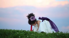 Little cute girl in dress squats and erase by eraser on pencil Stock Footage