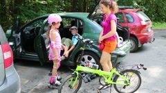 Mother, son and daughter prepare to ride bicycle and rollers Stock Footage