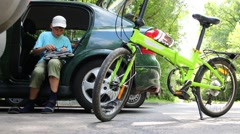 Boy gets ready to ride on roller skates in car next to bike Stock Footage