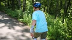 Teenage boy in helmet roller-skates on walkway in summer park Stock Footage