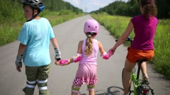 Back of boy and girl roller-skate and mother rides bike on road Stock Footage