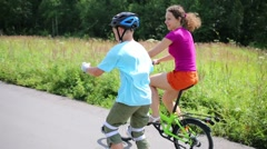 Boy in helmet roller-skates and mother rides bike at summer day - stock footage