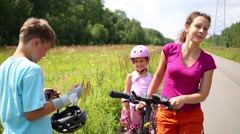 Boy and girl and mother with bike stand near road Stock Footage