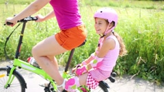 Happy girl in helmet sits on trunk of bicycle of mother Stock Footage