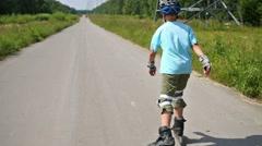 Teenage boy in helmet roller-skates on road in summer day Stock Footage
