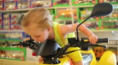Little boy in yellow sits on toy motorcycle in store with toys Stock Footage