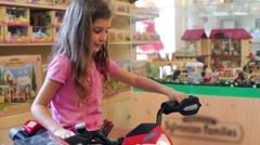 Girl sits on toy motorcycle in Children Gallery Jakimanka. Stock Footage