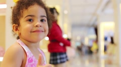 Little girl thumbs up and smiles in children store Stock Footage