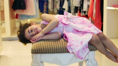 Little girl sleeps on pouf in children store with clothes Stock Footage