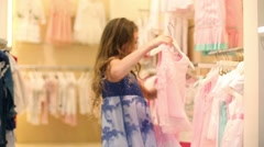 Girl looks at clothes and takes skirt with blouse in Gallery Stock Footage