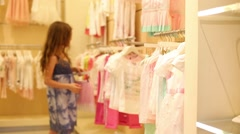 Girl looks at clothes in Children Gallery Jakimanka Stock Footage