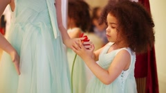 Little girl puts flower to hand of mannequin in Gallery Stock Footage