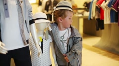 Little boy stands with mannequins in children clothing shop Stock Footage