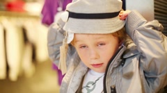 Boy wears hat near clothes hangers in children clothing shop Stock Footage