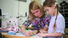 Tailor teaches student girl use of templates near sewing machine Stock Footage