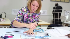 Tailor with pencil works with patterns for clothes and smiles Stock Footage