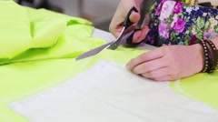 Female tailor hands cut light green cloth on table Stock Footage