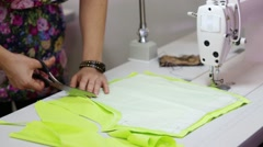 Female tailor hands cutting light green cloth on table Stock Footage