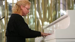 Woman plays white grand piano in competition of readers GIVE HEAT - stock footage