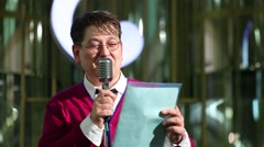 Man recites poetry into microphone in competition of reciters - stock footage