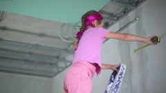 Little girl stands on ladder with ape rule in repaired apartment - stock footage