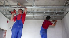 Stock Video Footage of Two men in uniform install framework for hung ceiling