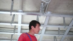 Man in uniform install framework for hung ceiling by screwdriver Stock Footage