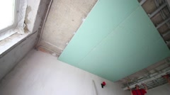 Stock Video Footage of Two workers install framework for hung ceiling in new flat