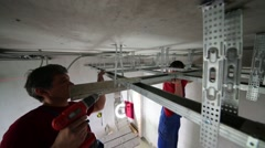 Workers with screwdriver, building level fasten ceiling profile Stock Footage