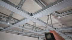 Stock Video Footage of Metal framework for hung ceiling and male hand hangs tape measure