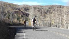 Bike riders on scenic mountain byway in autumn 4K 037 Stock Footage