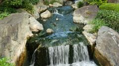 Waterfall runs into a Koi pond at Sensoji Temple Tokyo Japan Stock Footage