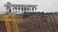 Wide Angle Shot of Pipes at an oil and gas Well Stock Footage