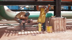 Wide Angle Shot of two oil and gas workers Stock Footage