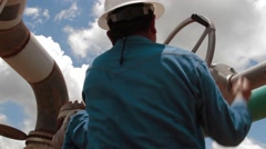 Low Angle of an oil and gas worker manipulating a valve Stock Footage