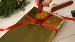 Christmas gift with golden wrapping paper getting sealed Stock Footage