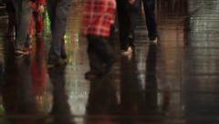 Crowd of people on streets of the city at night. Many feet on the wet asphalt. Stock Footage