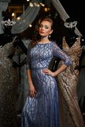 fashionable woman in blue dress with rhinestones and mannequins - stock photo