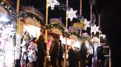 Christmas marketplace (shops) with people - decorations - building in background Stock Footage