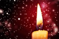 Twinkling stars against candle burning - stock photo
