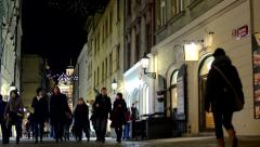 urban street with shops - people walking - christmas decorations - night - stock footage