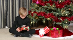 Child guessing what is in a Christmas present Stock Footage