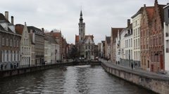 Tourist canal boat turning on a canal in Bruges, Belgium Stock Footage