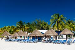 caribbean beach with sun umbrellas and bed - stock photo