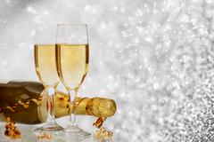 Champagne against fireworks and holiday lights Stock Photos