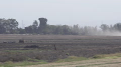 Wide shot of a pair of Tractors Plowing a Field Stock Footage