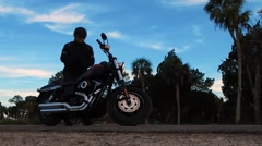 Man getting on motorcycle/riding off Stock Footage