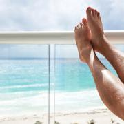 Tanning legs in hotel terrace over sea view Stock Photos