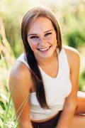 portrait of an attractive young woman sitting in grass laughing and smiling - stock photo