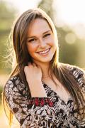 portrait of attractive young woman in dress hand on neck - stock photo